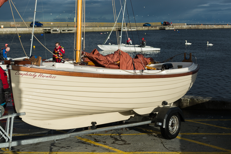 "This boat, with its burnt orange sail, stood out among its peers while out at see. Not quite so resplendant after being hauled ashore. In fact, ""Completely Harmless""!"